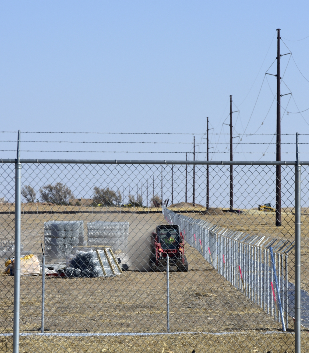 A worker prepares to gather supplies from the laydown area as construction of the perimeter fence continues on Nov. 6, 2019, at the site of the Johnson Corner Solar Project in Stanton County near Johnson City, Kan.