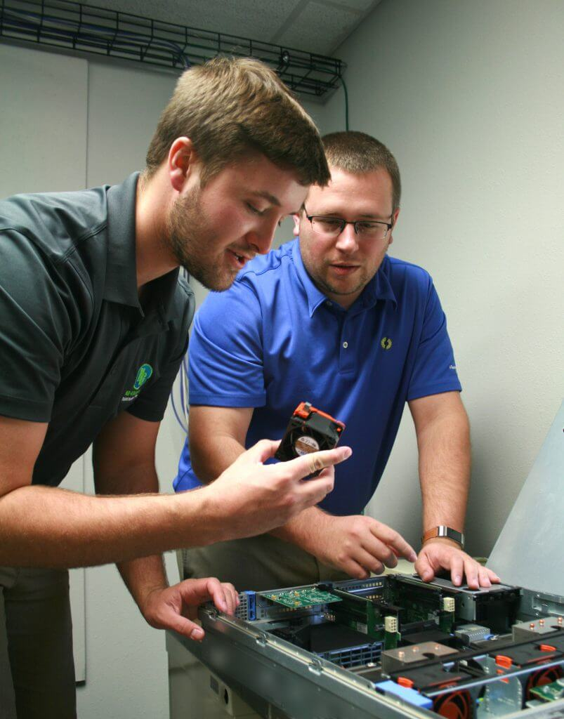 Ernie Pfeifer, computer systems administrator at Sunflower Electric Power Corporation, right, works with Zach Young, a Sunflower intern, as they work together on a server on Friday, July 20, 2018, at the Sunflower's office in Hays. (Photo by Steven Hausler, Sunflower Electric Power Corporation)